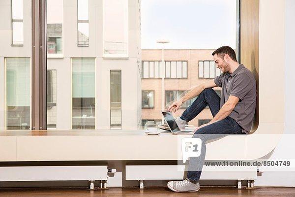 Geschäftsmann auf der Fensterbank sitzend mit Laptop