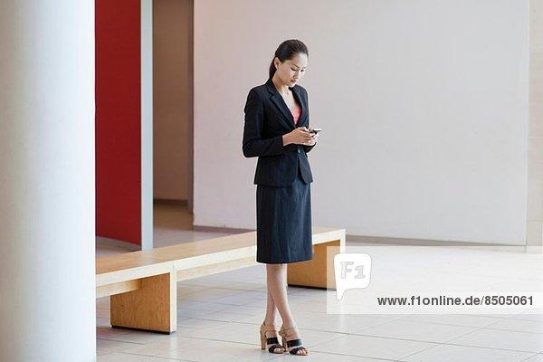 Geschäftsfrau im Wartebereich des Büros  mit Smartphone