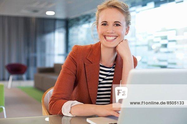 Businesswoman sitting at desk  using laptop
