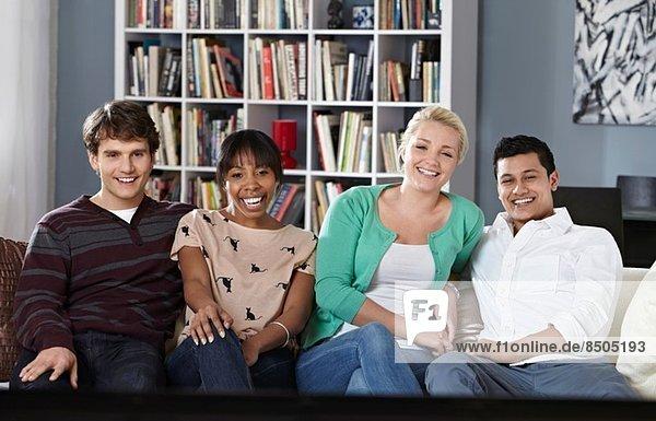 Junge Leute sitzen auf dem Sofa und schauen fern.