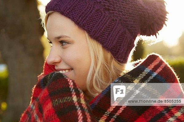 Portrait of young woman in park  tartan picnic blanket around shoulders