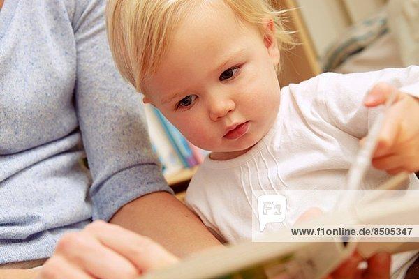 Mutter liest Bilderbuch mit Baby-Tochter