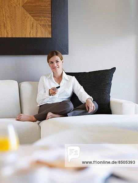 Porträt einer jungen Frau  die mit Fernbedienung im Hotelzimmer arbeitet