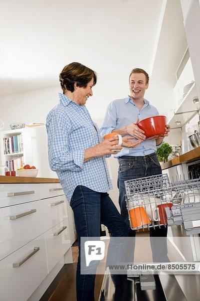 Erwachsener Enkel hilft Großmutter in der Küche
