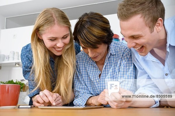 Großmutter betrachtet digital mit erwachsenen Enkeln