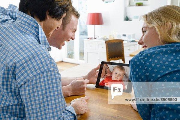 Großmutter und erwachsene Enkelkinder betrachten Foto des kleinen Jungen auf digitalem Tablett