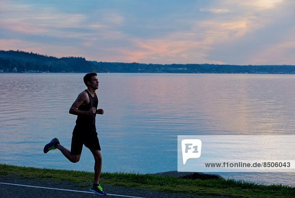 Jogger running past lake