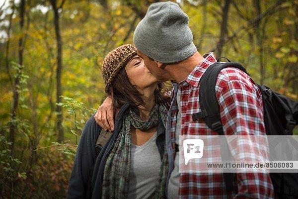 Reife Paare beim Küssen im Wald