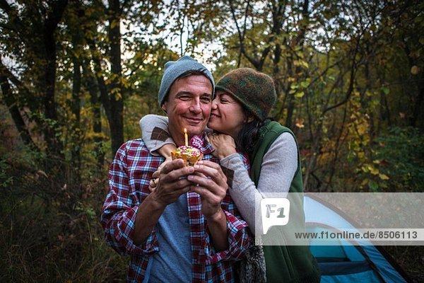 Ein reifes Paar im Außenzelt mit Geburtstagskuchen