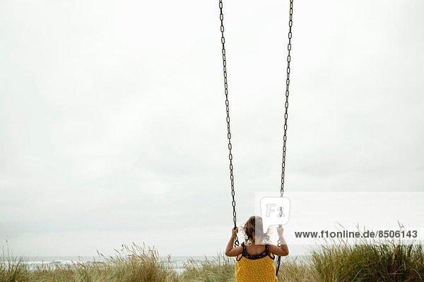 Weibliches Kleinkind auf Strandschaukel