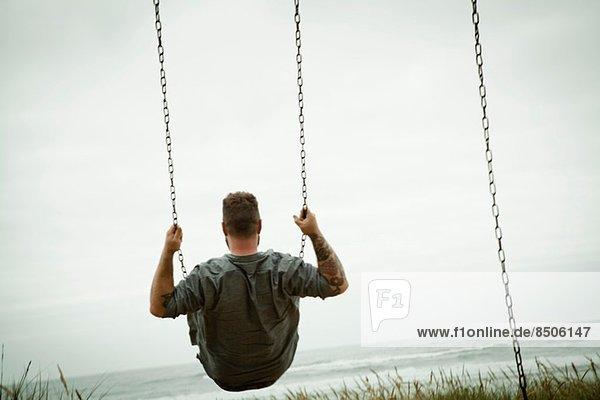 Mittlerer Erwachsener Mann auf Strandschaukel
