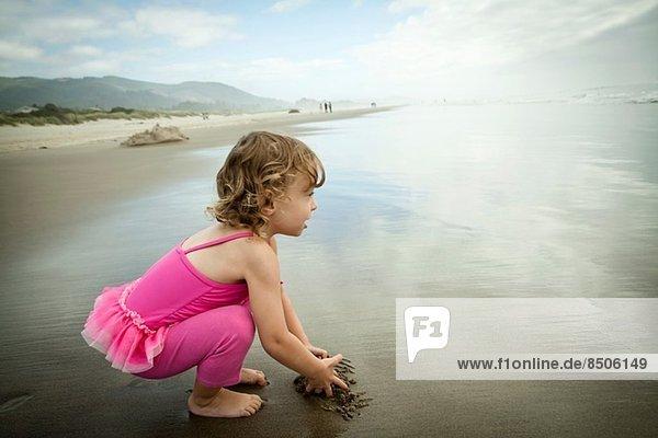 Porträt einer im Sand spielenden Kleinkindin