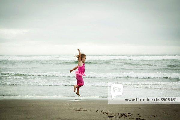 Weibliches Kleinkind beim Springen am Strand