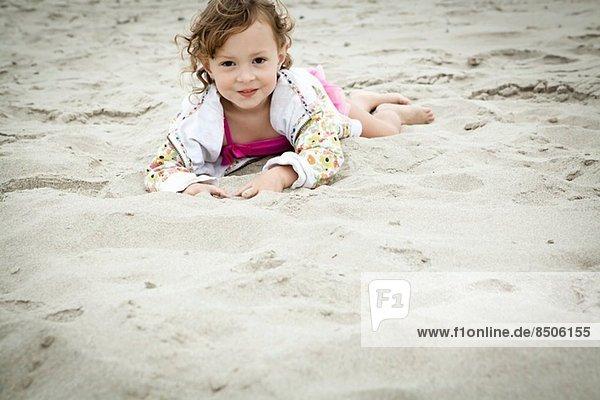 Portrait eines im Sand liegenden Kleinkindes