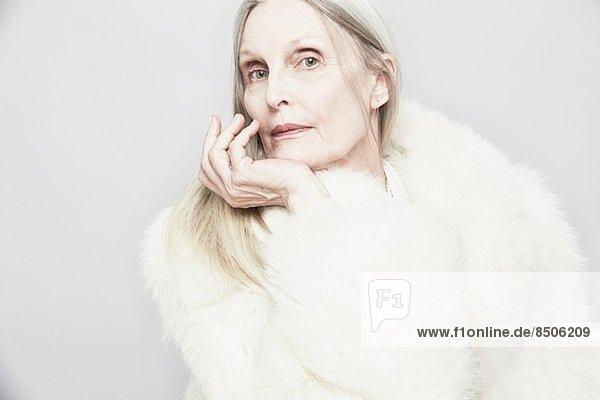 Abgeschnittenes Studioporträt einer älteren Frau mit Hand am Kinn