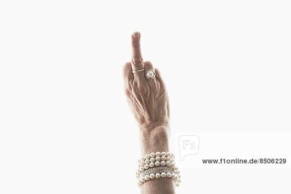 Studioaufnahme der Hand einer reifen Frau  die eine obszöne Geste macht.