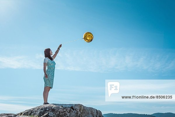 Mature woman standing on rock with golden balloon