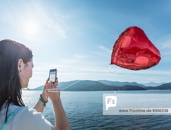 Mature woman photographing heart shaped balloon
