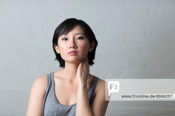 Atelierporträt einer jungen Frau mit Hand am Hals