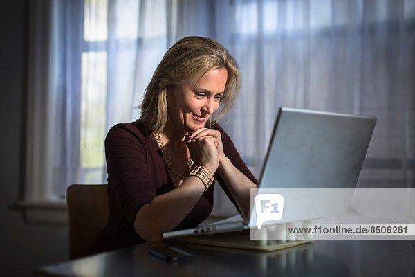 Reife Frau zu Hause sitzend mit Laptop