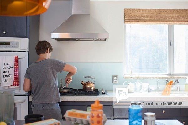 Reife Frau bei der Zubereitung von Speisen in der Küche