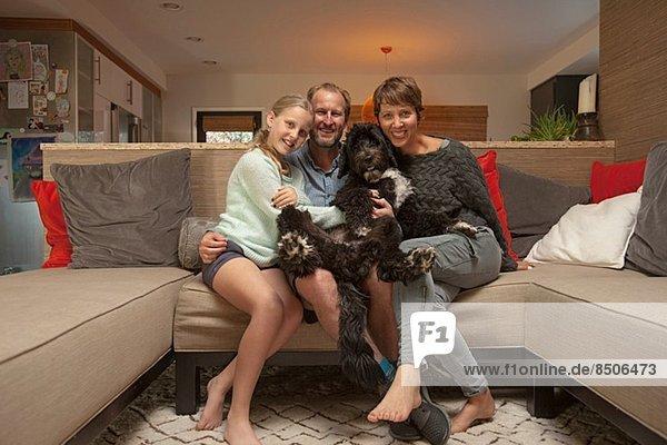 Porträt von Eltern  Tochter und Hund auf Sofa