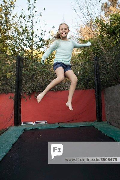 Mädchen mit Spaß auf dem Gartentrampolin