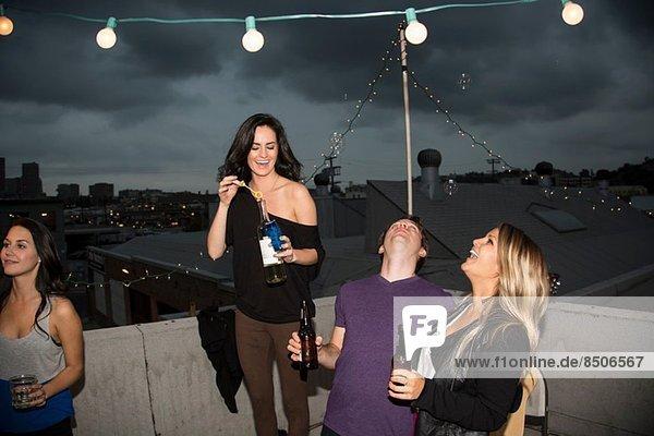 Junge erwachsene Freunde blasen Blasen auf der Dachparty
