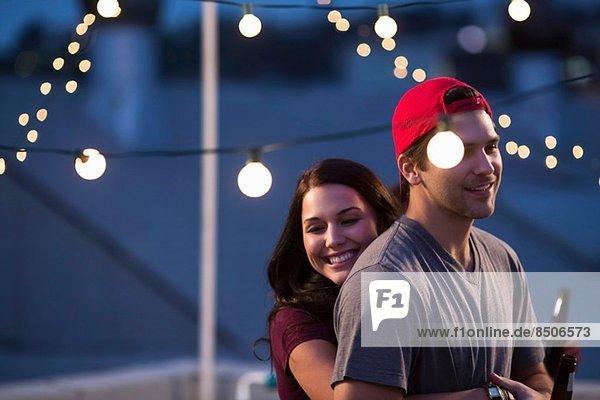 Junges Paar umarmt sich am Dachgrill