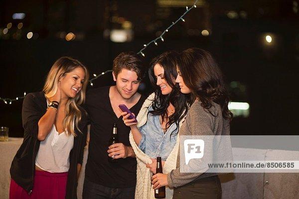 Junge erwachsene Freunde schauen auf das Handy auf der Dachparty
