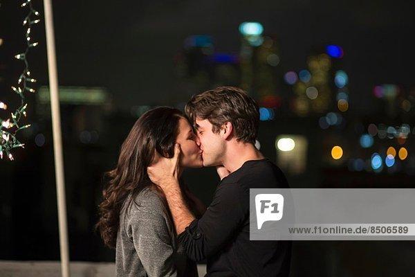 Junges Paar küsst sich auf der Dachparty