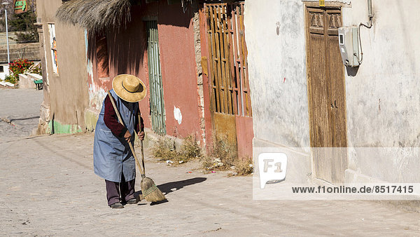 Woman sweeping outside her house  Putre  northern Chile