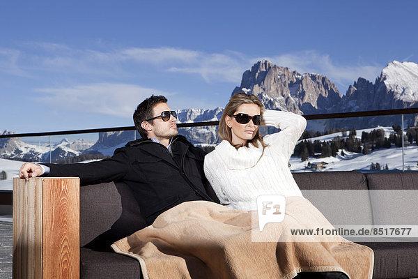 Mann und Frau sitzen auf einer Couch im Freien  Seiser Alm  Südtirol  Italien