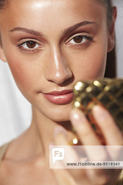 Close-up of glamorous young woman with glowing skin holding a compact mirror