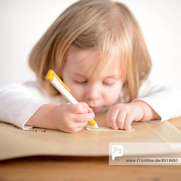 Ein Kind hält einen Kugelschreiber in der Hand und malt.