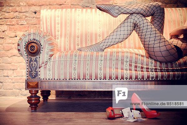 Eine Prostituierte sitzt auf einem Sofa.