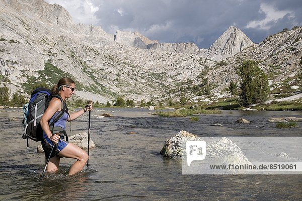 Woman crosses Evolution Creek on John Muir Trail