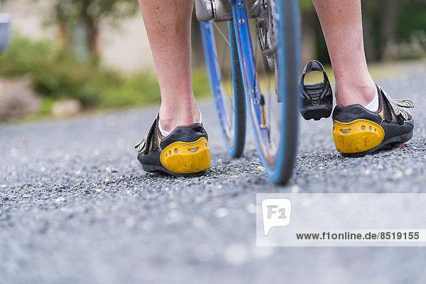 USA  Texas  Beine eines Radfahrers auf Asphalt