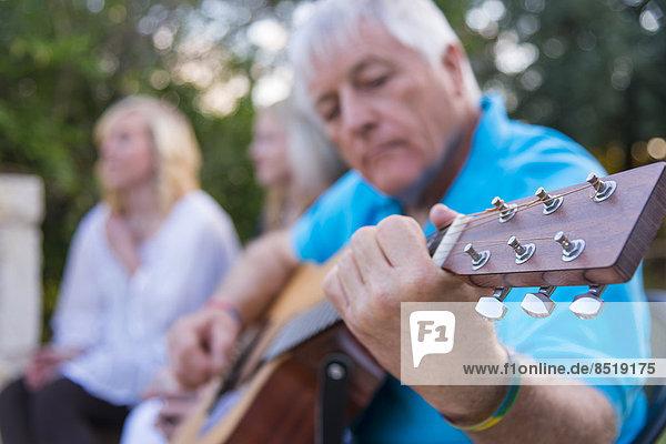 USA  Texas  Senior Mann spielt Gitarre mit Teenagern im Hintergrund
