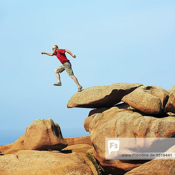 France  Bretagne  Tregastel  Man jumping on rocks