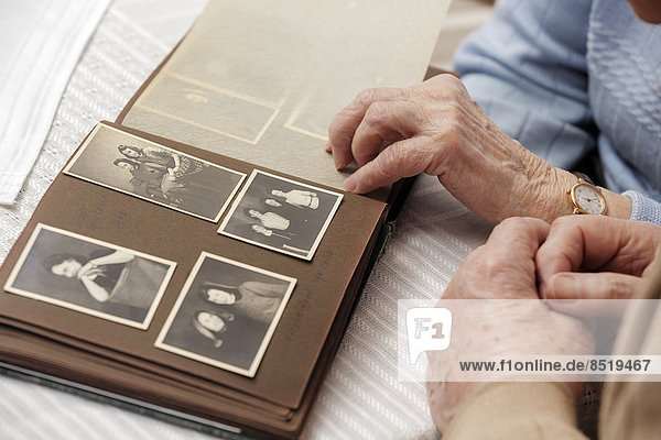 Senior couple watching old photograph album at home