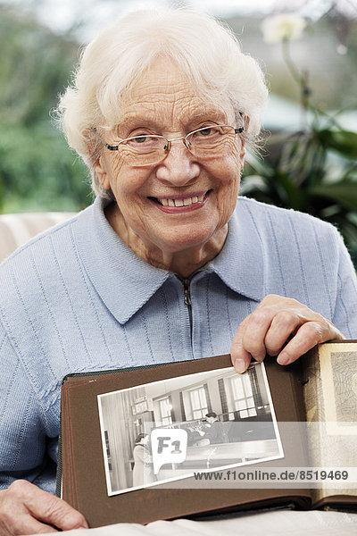 Ältere Frauen zeigen ein altes Foto von sich selbst