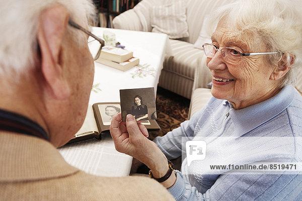 Seniorin zeigt ihrem Mann ein altes Foto von sich selbst