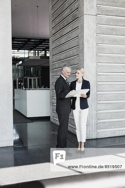 Geschäftsmann und Geschäftsfrau mit im Amt sprechenden Dokumenten