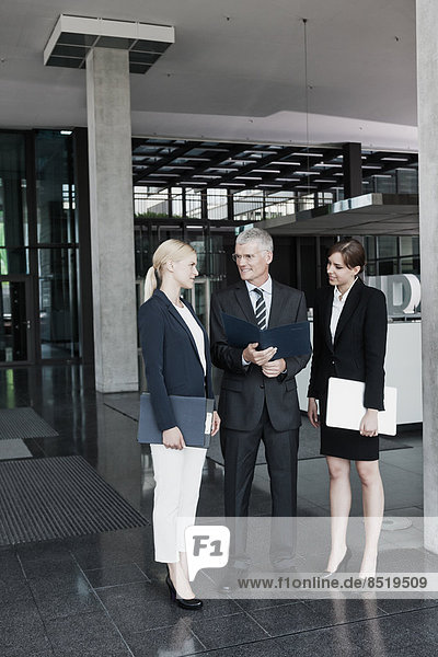 Three businesspeople with documents talking in office