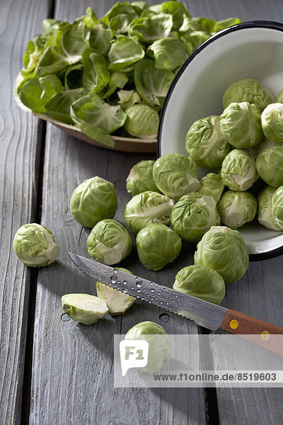 Bowl of Brussels sprouts  plate with peels and kitchen knife on grey wooden table