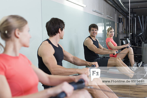 Austria  Klagenfurt  Man and woman exercising with rowing machine