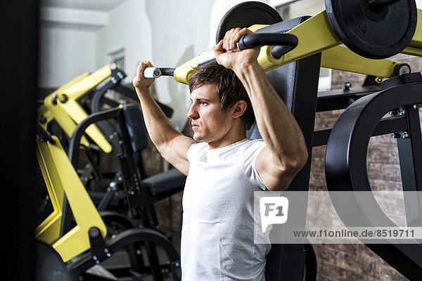 Austria  Klagenfurt  Man in fitness center doing machine workout