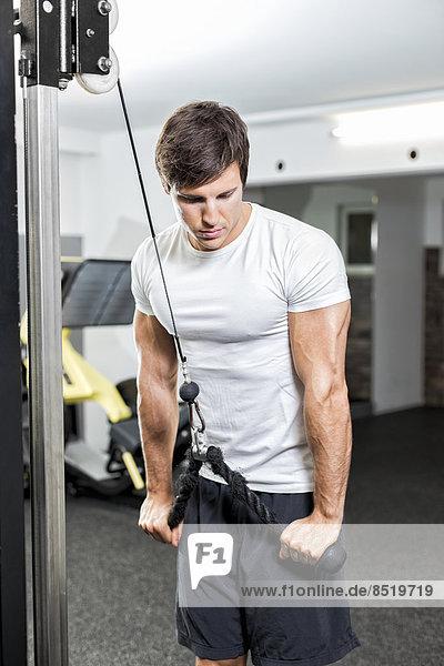 Österreich  Klagenfurt  Mann im Fitnesscenter beim Kabeltraining