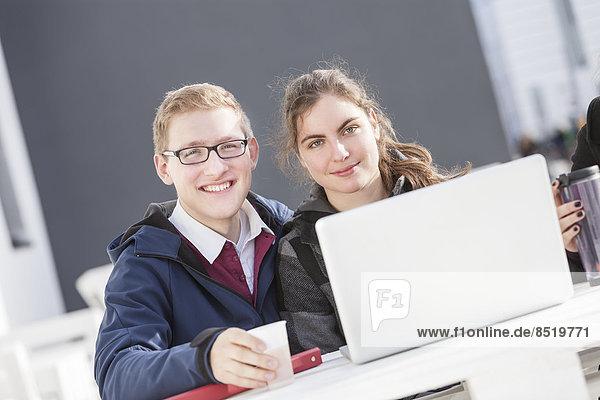 Zwei lächelnde Studenten mit Laptop im Freien  Portrait